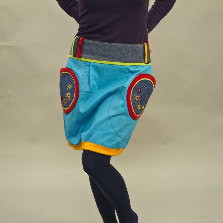 """Sukně """"Cyan 2"""" Originální, veselá, hravá sukně, navržená v kombinaci plátna, džínoviny a úpletu. Na džínových kapsách zdobená dírkováním s ručním obšitímv několika barevných odstínech. Sukni doporučuji nosit spadlou na boky.Zapínání vzadu na zip a 2 knoflíky. Sukně je přes boky volná, takže se přizpůsobí různým postavám. Velikost na objednání - ..."""