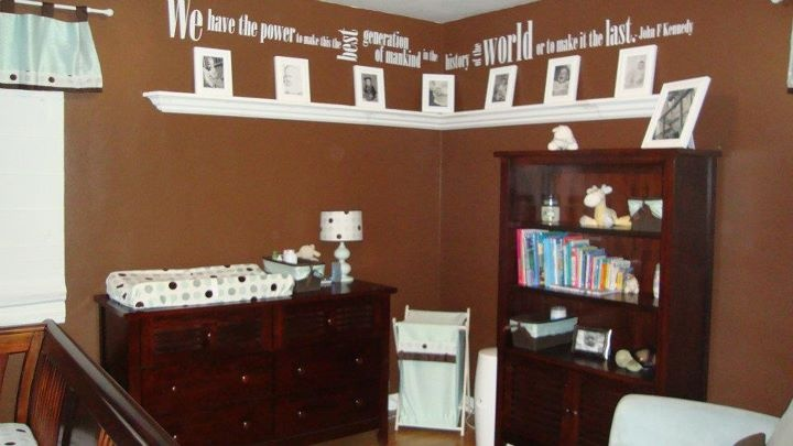 "A friend's baby room. The shelf features their ""generations wall"" with pictures of family and space for baby pictures. Above the pictures is a quote about generations from JFK."