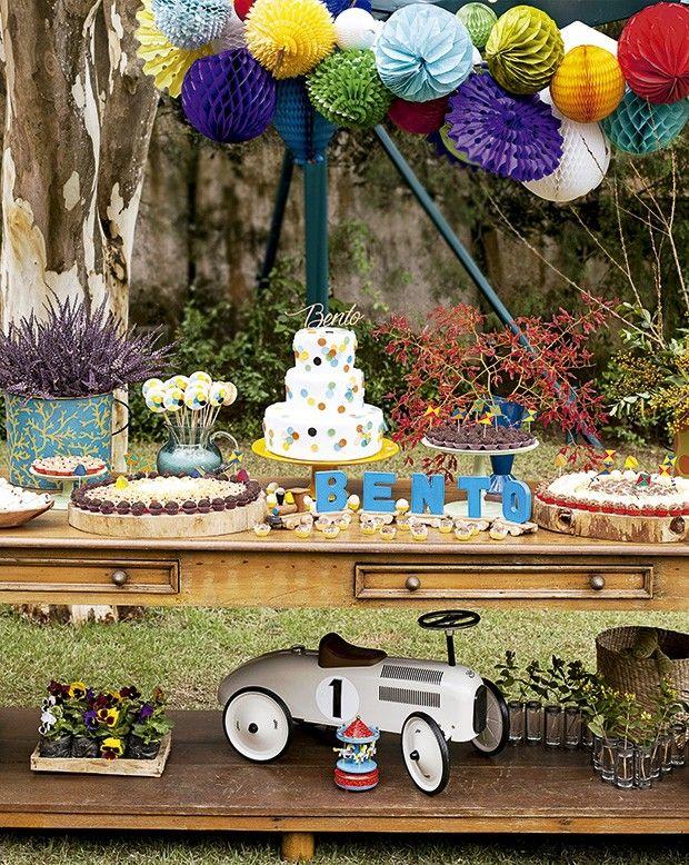 A mesa do bolo: brinquedos do aniversariante entraram na decoração e delicados globos de papel de seda substituíram o arco de bexigas (Foto: Elisa Correa/Editora Globo)