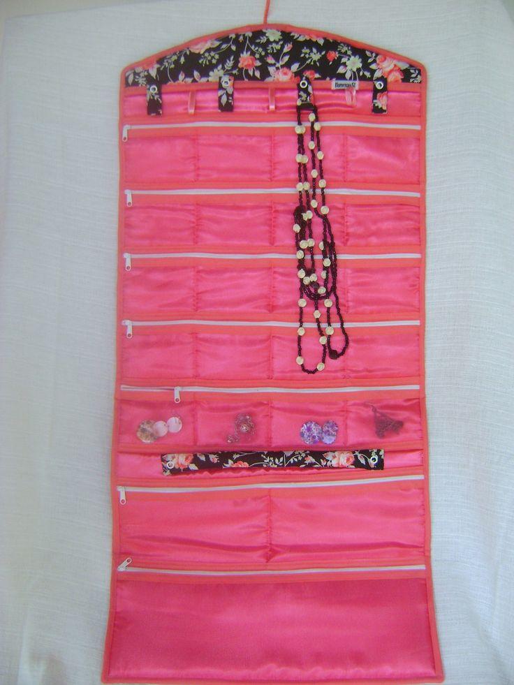 Organizador de j�ias e/ou bijuterias feito em tecido 100% algod�o. Fechado, ele mede aproximadamente 40cm de largura por 25cm de altura, ocupando pouco espa�o, principalmente se voc� for viajar. Aberto mede aproximadamente 40cm de largura por 86cm de altura, podendo ser pendurado, expondo seu conte�do e facilitando o acesso aos objetos. Tem uma aneleira, 7 ganchinhos para colocar correntes, colares, pulseiras ou tornozeleiras, 20 bolsinhos pequenos, 2 m�dios e 1 grande, todos confeccionados…