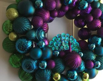 Peacock Christmas Ornament Bulb Wreath, Purple, Teal, & Green  Beautiful and unique Christmas Wreath that you just have to have! The wreath can be left out all year round due to the nature it's design. There is even a peacock in the center! This would be a great addition to your holiday decor. You can hang in on your door, in front of a mirror, or even on your mantle.