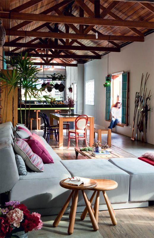 """Banquinhos Abaporu (Dpot) e sofá modular da Tok Stok. Ao redor da mesa de jantar (Tok Stok), cadeiras Thonet (Isto É Brasil). As generosas aberturas de 1,30 x 1,90 m ficam a apenas 35 cm do chão: """"Fiz questão de ter janelas onde eu pudesse me sentar."""""""