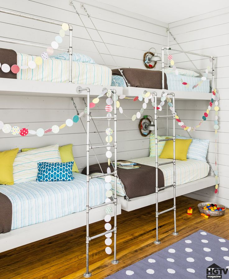 If you think the holiday decor stops at the living room and kitchen, think again. Joanna highlights the metal piping and cable bunk beds she designed with festive paper garlands. Cute, right?  Outdoor sconces bring the farmhouse feel to the bedroom. The polka-dot rug is from The Land of Nod, and the striped bedding is from Target. See the full house tour at HGTV.com!