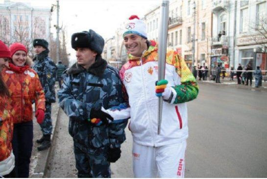 Canadian Craig Cohon, right, carries the #Sochi2014 Olympic torch into Krasnoyarsk, Russia.