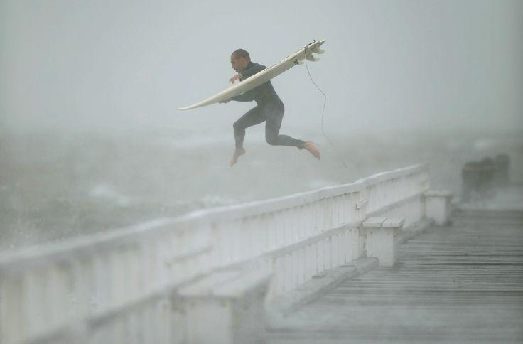 Peselancar memanfaatkan gelombang laut, saat badai melanda kawasan pantai Melbourne, Australia.