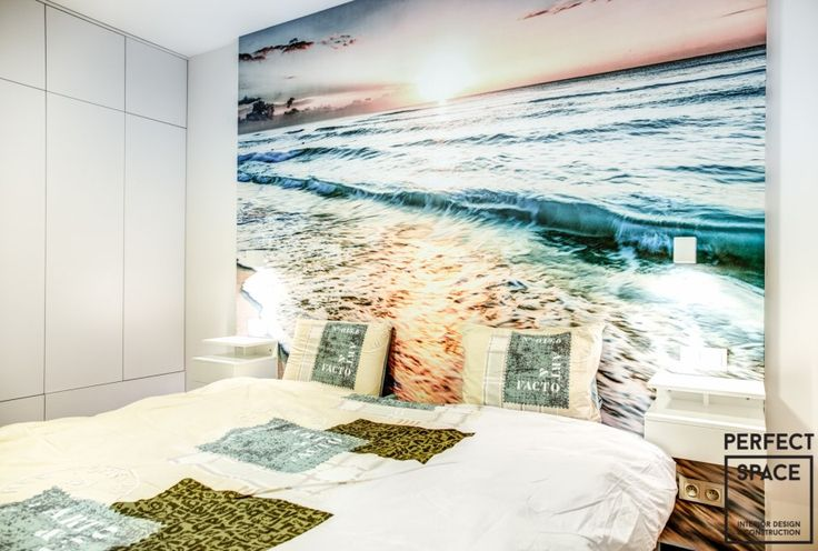 Fototapeta z widokiem na morze ii zachodzącym słońcem umieszczona nad łóżkiem nadaje przytulnego charakteru temu wnętrzu.
