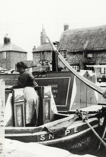 BW192-3-2-2-13-1-456 a close up of the stern of the butty 'Snipe', there is a boatwoman stood by the entrance to the cabin. The motor 'Tern' is behind 'Snipe' and has a decorated can on top of the cabin. The Boat Free House and cottages are visible in the background. [The narrowboats are the ex Fellows, Morton & Clayton Limited boats 'Kildare' and 'Emu']. Date 1950s
