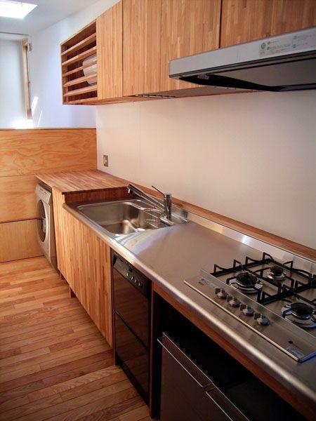 格安オーダーキッチン施工例 鎌倉Y邸のキッチンです。コストを徹底的に考えてつくりました。扉は集成材で天板はステンレスのオーダー品。収納は最小限にして、無印良品のワゴン(現在は廃盤)を活用しています。収納を節約した一方で、洗濯機やエアコンはキッチン内に設置できるようにしました。食洗機は、今はなき、ホシザキの特急すすぎ。あっという間に終わる優れものだったんですが、ホシザキは戸建住宅から撤退してしまいました。コンロはリンナイのグリルなしのタイプを選んでいます。