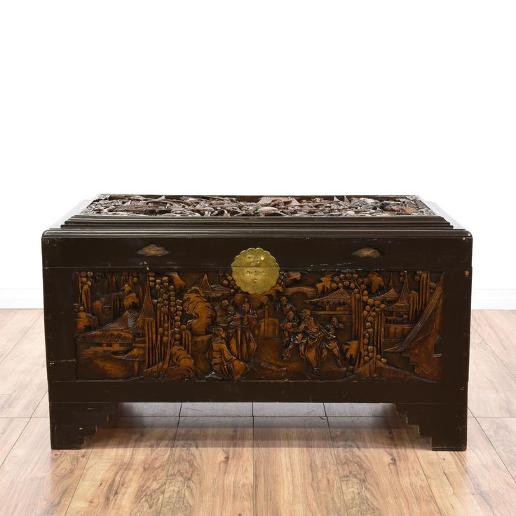 This Chinese trunk is featured in a sold wood with a dark walnut finish. This ornate chest has intricate carved battle scenes and landscapes with a large interior cabinet and brass front hardware missing the latch, but safer for children. Perfect blanket chest for accenting a room! #asian #storage #chestortrunk #sandiegovintage #vintagefurniture
