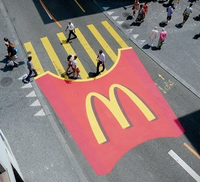 Here we have the McDonald's logo on the street that many in the world are familiar with. Advertisements companies will do anything to sell their product or promote it. In this picture we see this ad and almost everyone knows what it is. People don't realize how ads control us and how they are around every minute of our lives.