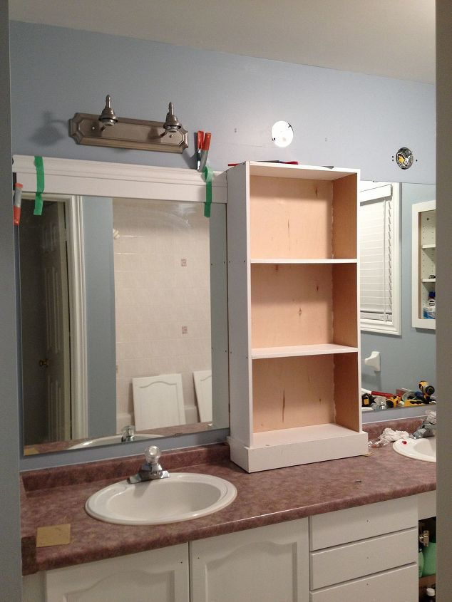 large bathroom mirror redo to double framed mirrors and cabinet, bathroom ideas, home decor, shelving ideas, middle cabinet in place new light fixtures connected and now onto the framing of the mirrors
