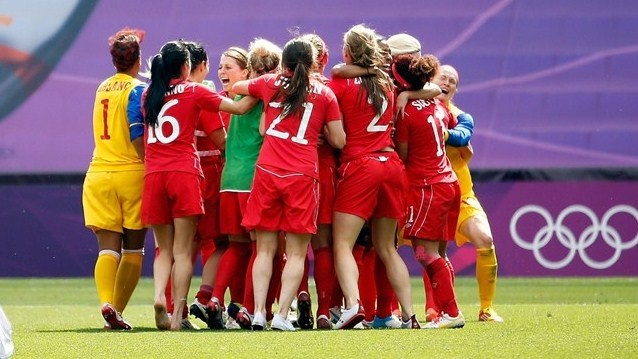 Players from Canada celebrate after defeating Camille Abily #10 and France to win the bronze medal during the women's football bronze medal match at City of Coventry Stadium.