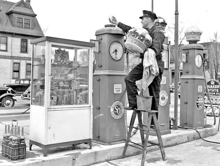 """Standard Oil Gasoline station 1939,The """"Stanolind"""" pump gets its light and pump globe serviced and cleaned. In the center is a Standard """"Red Crown"""" pump and on the far-right the high-test """"Solite Gasoline with Ethyl."""" This image includes a gasoline pump """"merchandiser"""" on the far-left."""