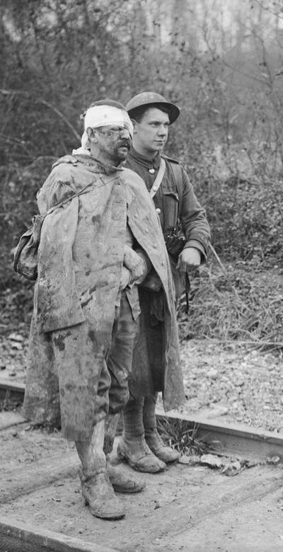 ©IWM (Q 4499) WWI,13 Nov 1916, Somme, Battle of the Ancre. A Military Policeman with a wounded German prisoner captured at St Pierre Divion. (Detail)