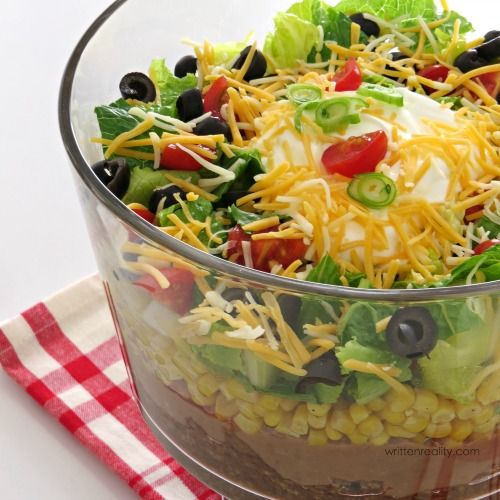 Easy Layered Taco Salad Recipe : Who doesn't love a great taco salad? This one is layered will all those Tex Mex favorites and topped with loads of cheese!
