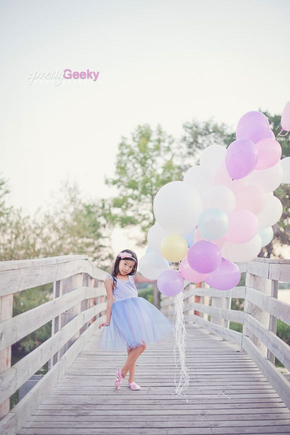 Little girl with lots and lots of pastel colored balloons