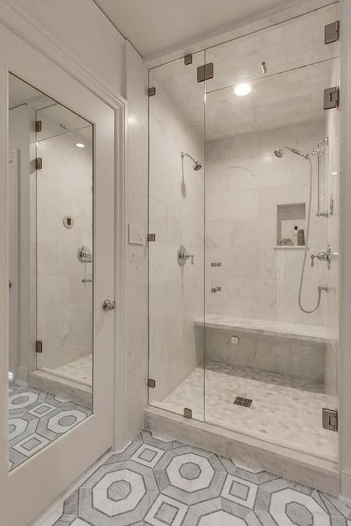White mirrored bathroom door reflects gray and white Walker Zanger Villa D'Oro hexagon floor tiles leading to a seamless glass walk in steam shower fitted with Calcutta marble wall tiles and marble hex floor tiles.