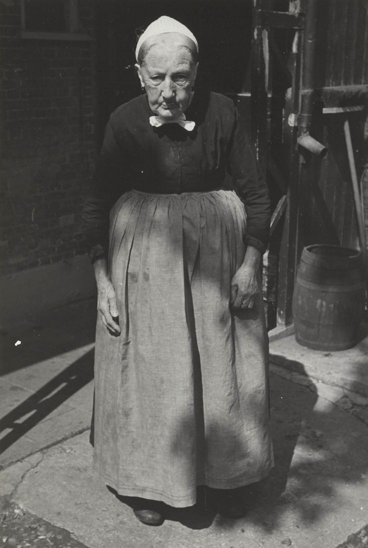 Maria van der Zwan-Moerman in Vlaardingse streekdracht (geboren 1862). Ze is gekleed in daagse dracht. Ze draagt een schootjak met lange schoot, rok, schort van verpleegsterslinnen met 'gatbanden' en een gehaakte muts. 1950 #ZuidHolland #Vlaardingen