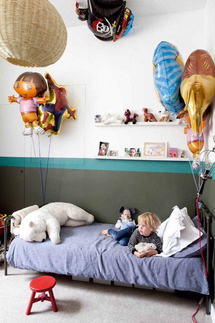 Dans la chambre de Roman, un lit et une suspension Serendipity et les ballons souvenirs d'un goûter d'anniversaire.