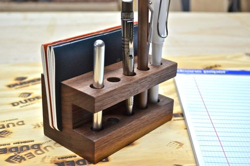 Handmade from solid walnut and finished in a soft, satin poly, this piece combines a place to hold 9 of your writing instruments up to 1/2 inch in diameter and a space to store/display three of your favorite pocket notebooks all in one tidy place.