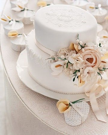 "The scale and shape of this cake suggest a gorgeous Victorian hat, so it's appropriate that the decorations adorning it are millinery flowers -- fabric blossoms that are traditionally used by hatmakers. Kromer's royal-icing ""string work,"" a stenciled top, and icing flocked with shimmery sanding sugar all add to the romantic feel. Favor boxes, by Denise Sharp, ornamented with fabric calla lilies are covered in custom paper."
