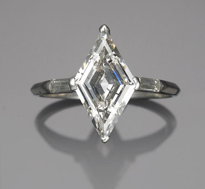 A diamond ring centering a lozenge-shaped diamond, weighing approximately: 1.00 carat; mounted in platinum;