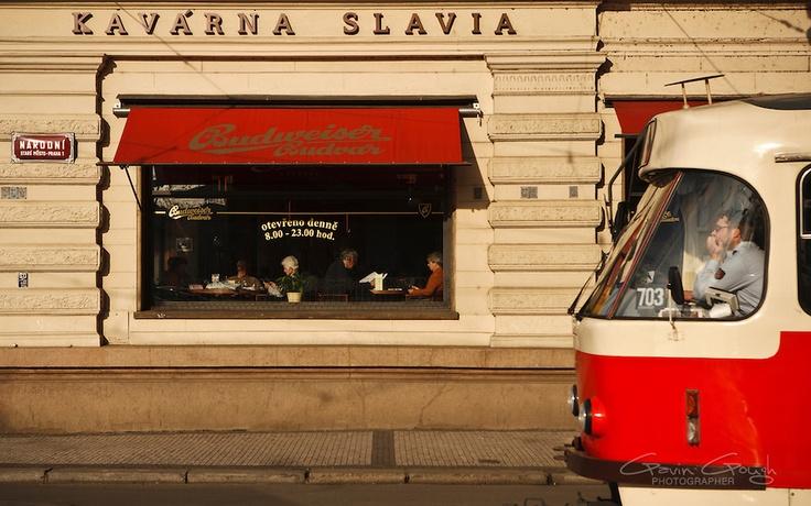 A tram driving past the Art Deco Kavarna Slavia cafe in Prague, Czech Republic