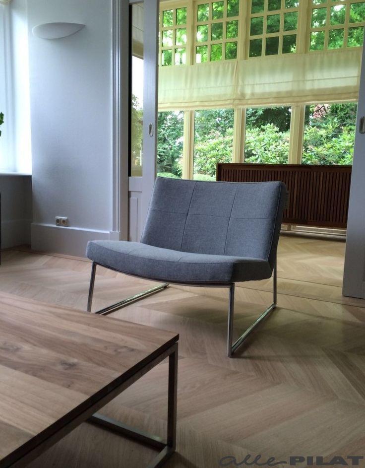 Moderne fauteuil Hebbes in een lichtgrijze stof en met een frame van chroom…