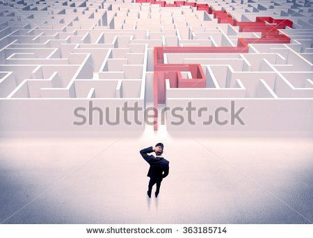 A businessman in suit giving thumbs up in front of labyrinth with red line showing the way out - stock photo