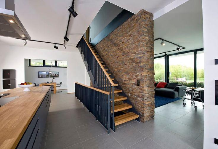 Escalier intérieur avec mur en pierre comme séparateur de pièce et escalier droit ouvert -…