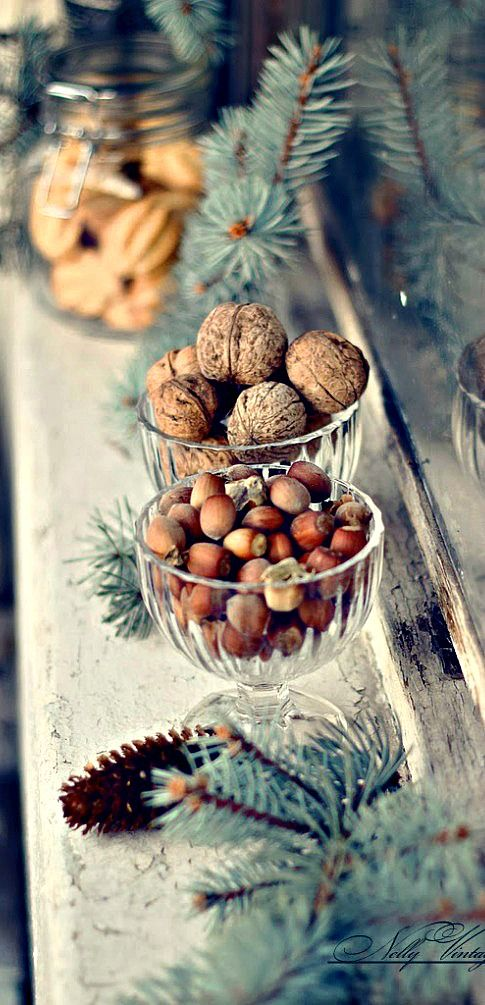 Glass Bowls of walnuts and hazelnuts and spruce on the mantle