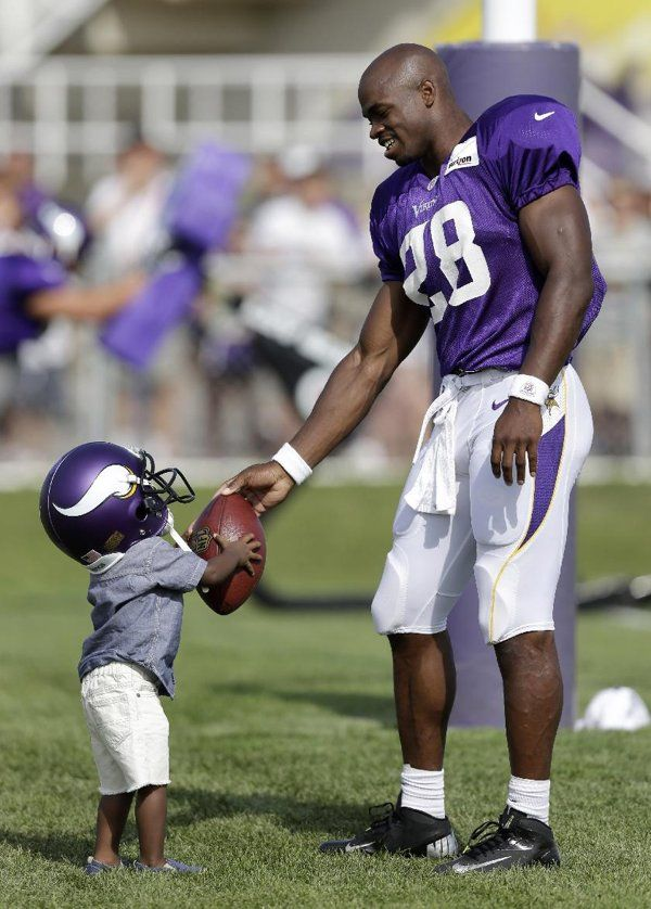 Minnesota Vikings running back Adrian Peterson hands a football to his son Adrian Jr. at the end of practice at NFL football training camp, Monday, July 29, 2013, in Mankato, Minn.