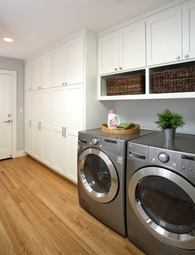 One tall cabinet at the end, counterspace with sink up to that, cabinets over washer/dryer.
