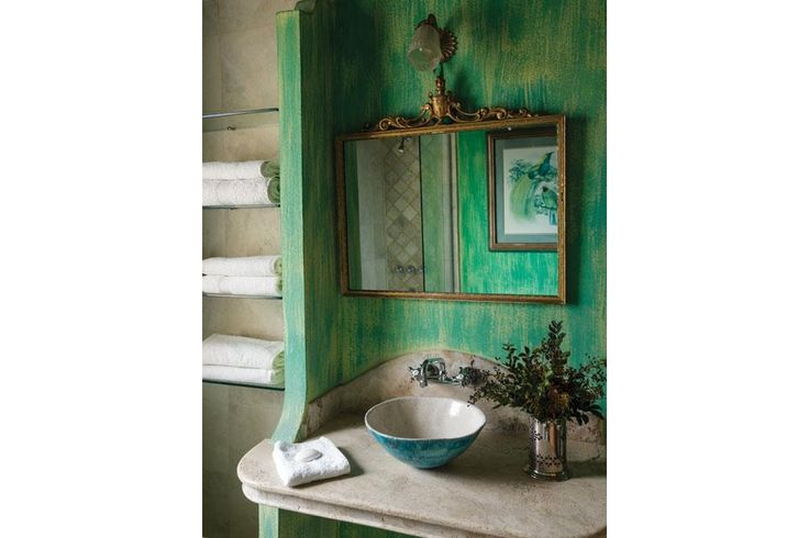 Una casa con estilo serrano  En el espejo se refleja una vieja lámina amarilleada por el sol que engamó perfecto con el tono de la pátina elegida. Junto al estante de toallas, mesada de mármol Travertino, bacha de cerámica y grifería de cocina.  /Daniel Karp