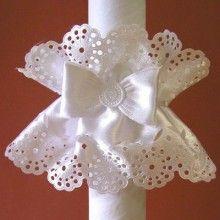 Okapnik na gromnicę nie musi być nudny! Może mieć formę stroika i być pięknym dodatkiem do stroju oraz świecy. Ten na zdjęciu dekorowany jest ażurowym wzorem i kokardą.
