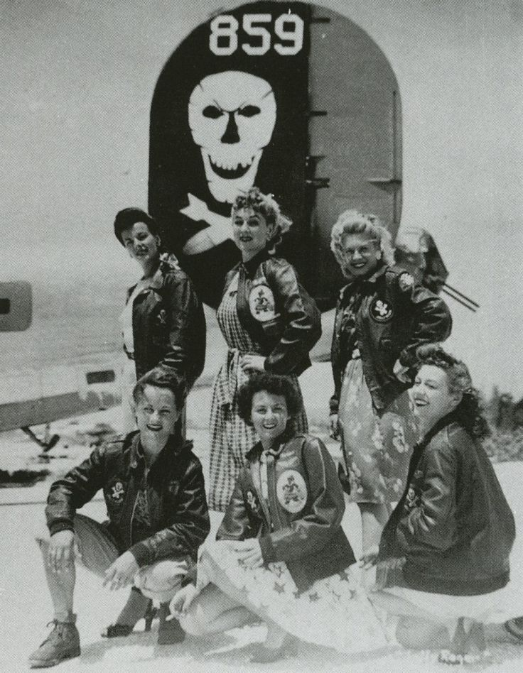 """Six U.S.O. Girls wear A-2 jackets belonging to the 90th Bomb Group, a.k.a. """"Jolly Rogers,"""" under a B-24 bomber."""