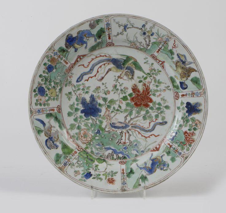 Plat en porcelaine et émaux de la famille verte. CHINE Famille verte- époque Kangxi (1662-1722)  A décor d'oiseaux Fenghuang en médaillon central. Le pourtour décoré d'animaux fantastiques et arbustes en fleurs. Marque Kangxi sur la base  Restauration Ce lot étant en importation temporaire une TAXE DE 5,5 % sera à payer par l'acheteur en plus des frais acheteurs.  Ø: 33.5 cm Adjugé: 300 €