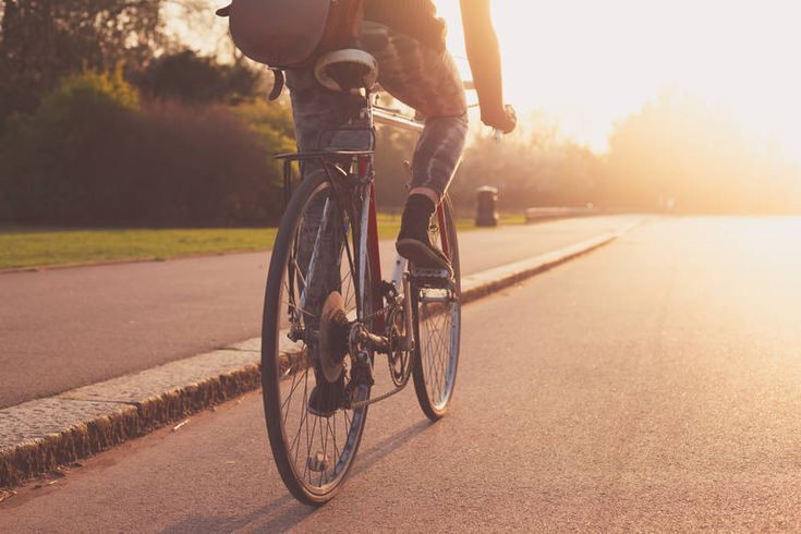 Riding a bike through a street at sunset
