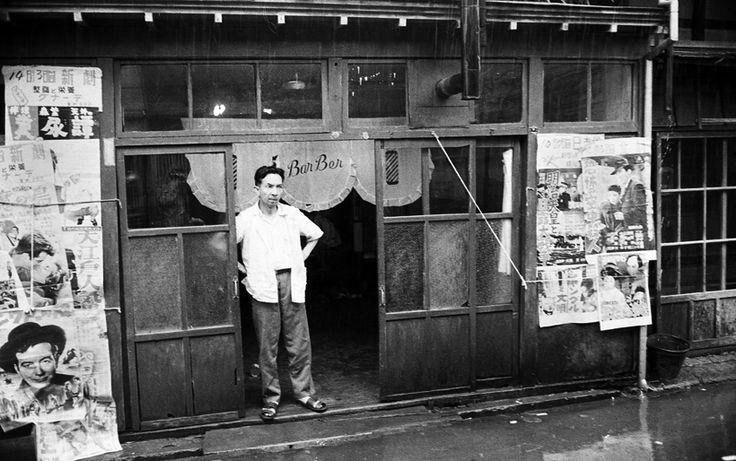 床屋 1957年7月。雨のためにお客さんが来ないのか店先で佇んでる、床屋のご主人                              …