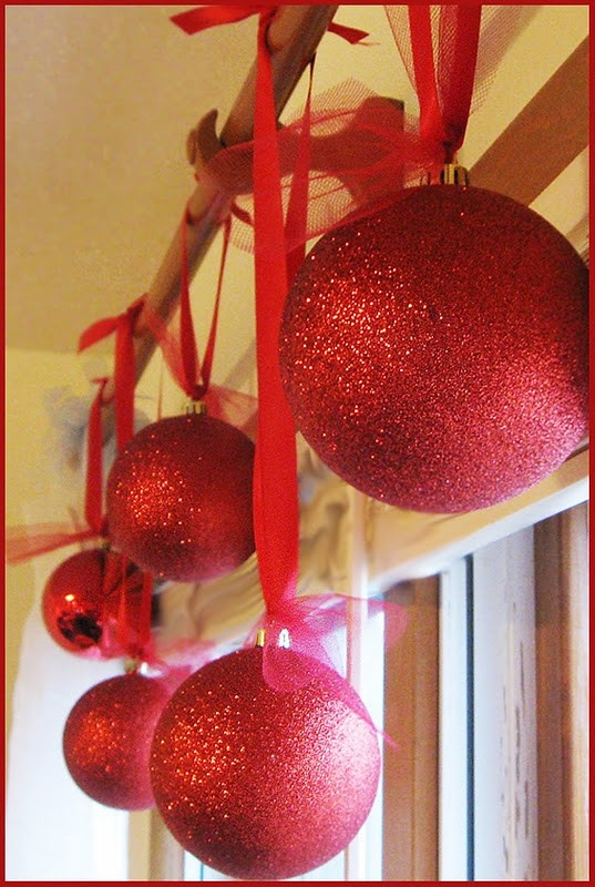 Huge ornaments hanging individually from curtain rod. Super cute!