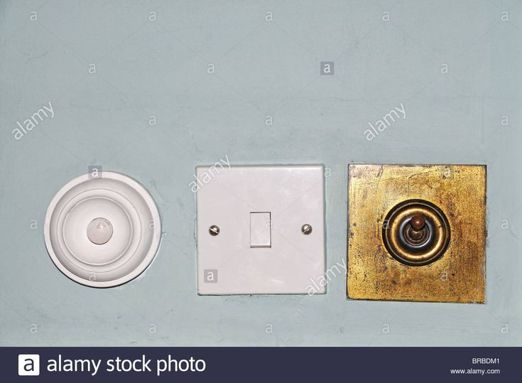 Download this stock image: Old brass  and new plastic light switches and room  service bell positioned in a row on a room wall. - BRBDM1 from Alamy's library of millions of high resolution stock photos, illustrations and vectors.