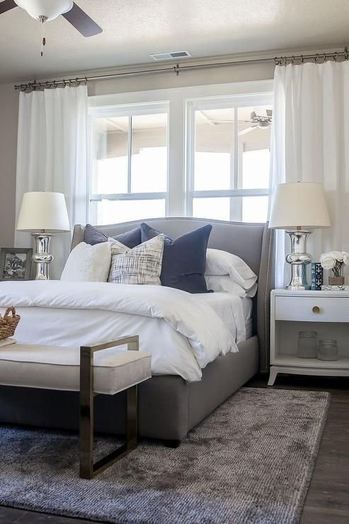 Beautiful bedroom features a gray wingback bed with silver nailhead trim dressed in soft white ...