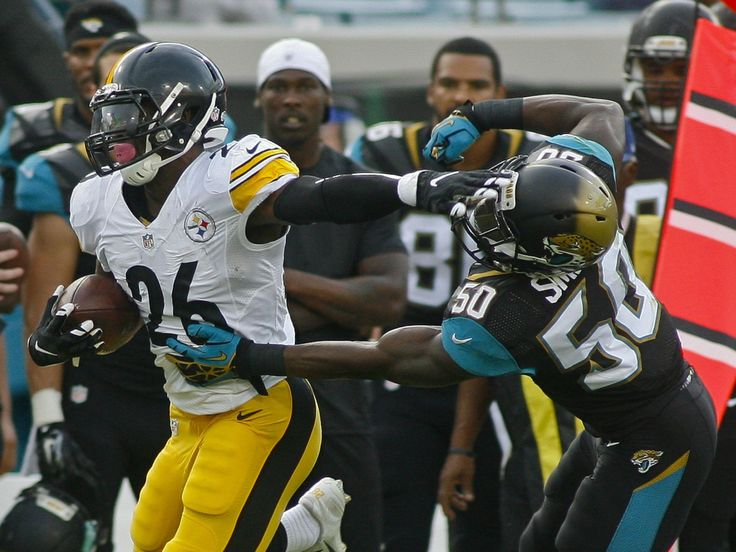 Pittsburgh Steelers running back Le'Veon Bell (26) stiff arms Jacksonville Jaguars linebacker Telvin Smith (50) on a long gain in the first quarter of a preseason NFL football game against the Jacksonville Jaguars at EverBank Field.  Phil Sears, USA TODAY Sports