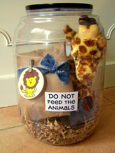 Empty cheese ball jar, stuffed giraffe and baby clothes - a see thru zoo for new baby. SUPER CUTE.