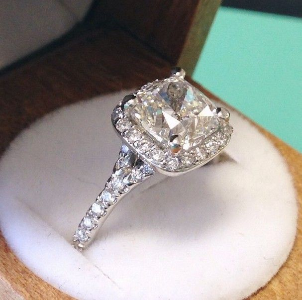 A glittering halo of pavé-set diamonds surrounds the center diamond in this elegant Brilliant Earth setting complete with a diamond-accented split shank band