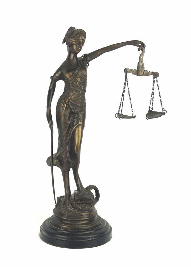 Een bronzen beeld van Vrouwe Justitia, op zwartmarmeren voet