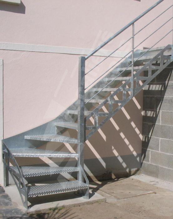 Photo DT72 - ESCA'DROIT® 1/4 Tournant Bas - Modèle déposé. Escalier extérieur d'accès terrasse au design contemporain et industriel en acier galvanisé. Marches en tôle larmée anti-dérapante. Limon intérieur découpé façon charpente métallique. Limon côté mur réalisé en tôle plane formant une plinthe protectrice. Rampe contemporaine composée d'une main courante en tube ergonomique et de 3 sous-lisses parallèles fines, montants en fer plat fixés en extérieur du limon. © Photo : Escaliers…