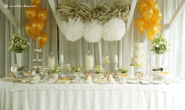 The dessrt table for this white and gold glamour baptism party