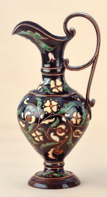 BADÁR BALÁZS (1855-1938) Kancsó Mázas keménycserép, kerek talpon álló kecses füles forma színesen festett virágmintás díszítéssel.