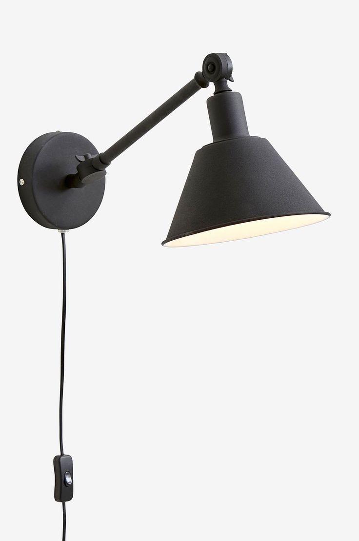 Vägglampa i matt målad metall. Skärmen är ledbar i höjdled och armen svängbar i sidled ut från väggen ca 50 cm. Vit lampa har vit sladd, svart lampa har svart sladd. Sladdlängd 2 m. Skärmens mått: Ø 20 cm. Höjd 12 cm. Stor sockel E27. Max 40 W. Ljuskälla ingår ej.